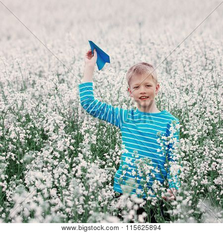 Young Boy With Paper Plane  And White Field Flowers
