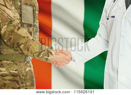 Military Man In Uniform And Doctor Shaking Hands With National Flag On Background - Ivory Coast
