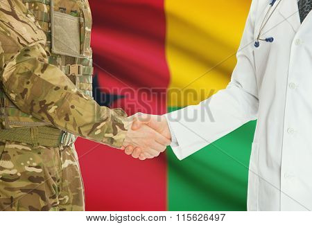 Military Man In Uniform And Doctor Shaking Hands With National Flag On Background - Guinea-bissau