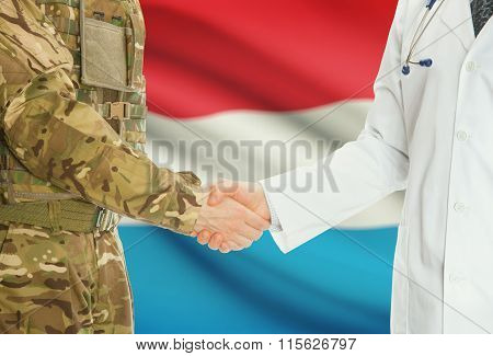 Military Man In Uniform And Doctor Shaking Hands With National Flag On Background - Luxembourg