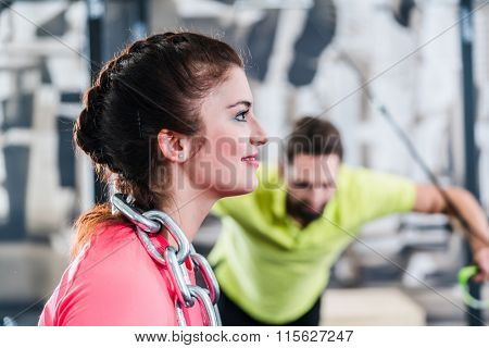 Woman at Functional Training with chain and rings in gym