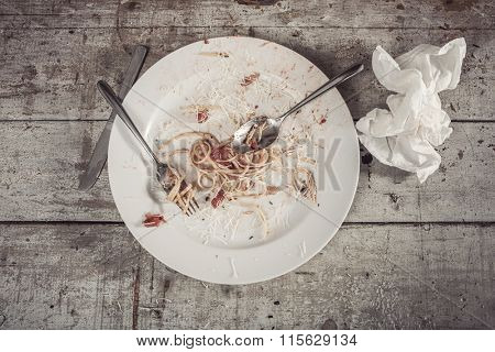 Plate of spaghetti at the end of a meal on a wooden table
