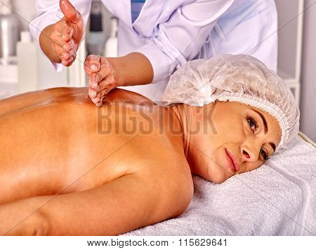 Woman middle-aged wearing cosmetic hat  take back massage in spa salon with young beautician.