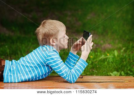 Cute Boy Lying In Park And Using Tablet Pc