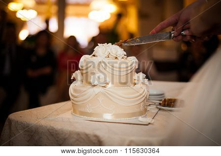 Tasty And Delicious Brown And White Tiered Wedding Cake Carved At Reception Closeup