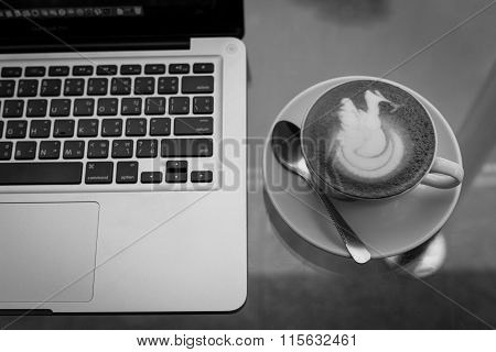 A Cup Of Coffee In A White Cup And Computer Labtop On Wooden Table