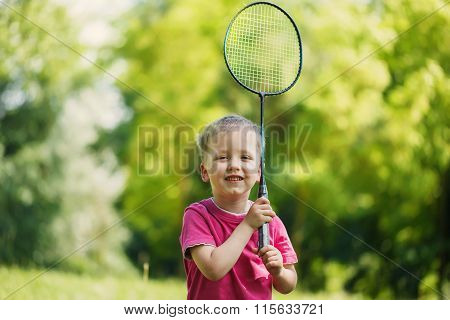 Little Cute Funny Kid Boy With Badminton Racquet Playing In Sunn