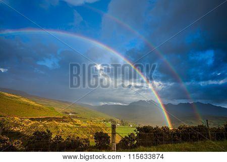 Rainbow sunlight on golden landscape Isle of Skye Scotland