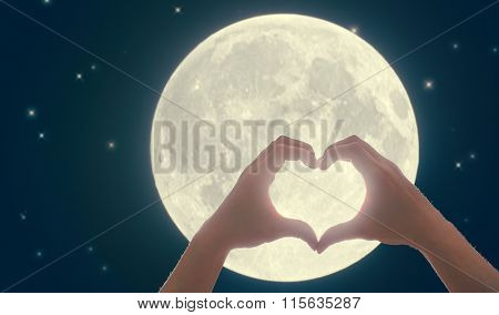 Male hands in the form of heart against the  dark sky, moon and stars . Hands in shape of love heart.  Wedding, Valentine, love concept.