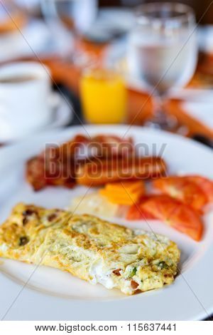 Delicious breakfast with omelet, bacon and vegetables