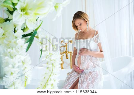Pregnant Girl In A White Lace Dress Sitting In The Interior With Flowers And Hugs Belly