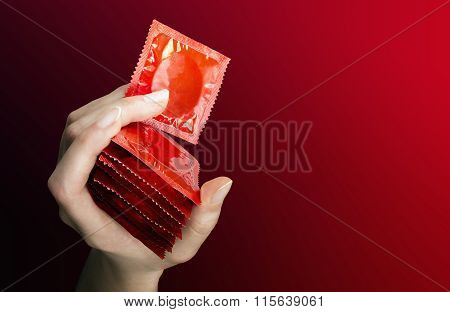 Woman's Hand With Seven  Red  Condoms