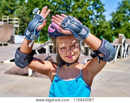 Girl wearing helmet riding on roller skates in skatepark.