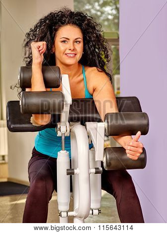 Girl with long curly hair workout on bicep curl machine in sport gym.
