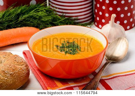 Carrot creme soup in orange bowl on the table.