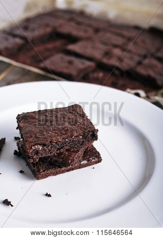 Brownie stack on a white plate and wood background
