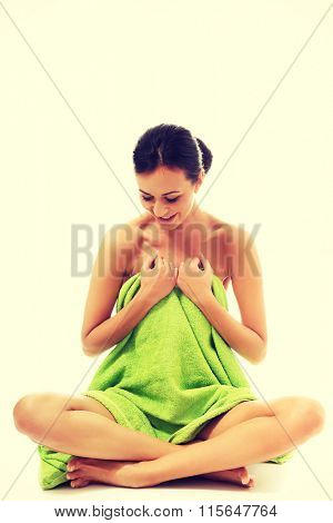 Woman sitting cross-legged wrapped in towel