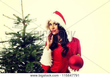 Woman in santa clothes holding christmas bubble