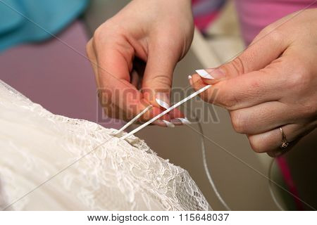 Bridesmaids Help Her Put On Wedding Dress
