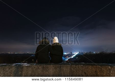 Loving couple looking at city night. Man and woman sitting in an embrace