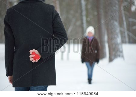 Surprise Valentines Day. Red decorative heart in his hand Man. Winter day in park