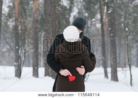 Romance Valentines Day. Happy couple kissing. Man holding a red decorative heart