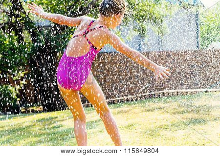 Little Girl Having Fun Under Water Drops.