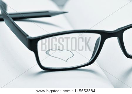 a heart drawn in a notebook seen through the lens of a black plastic-rimmed eyeglasses, in duotone