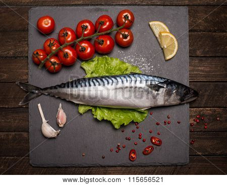 Top View Of Fresh Raw Whole Fish Mackerel On Slate Cutting Board Surrounded By Fresh Herbs And Spice