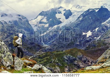 Female hiker standing on mountain on hiking trek. Side view of woman in warm clothing carrying backpack. Woman is enjoying idyllic view of mountain range.