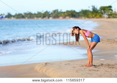 Exhausted runner relaxing on beach after running. Tired young woman is resting after jogging on sunny day. Full length side view of female in sportswear is looking away.