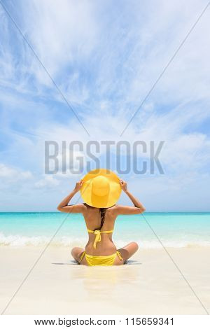 Beach Travel Vacation Holidays Woman Relaxing. Woman sitting on sea shore during summer. Rear view of female wearing yellow sunhat and bikini. Carefree tourist is enjoying vacation at beach.