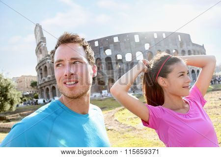 People Running  by Colosseum in Rome. Jogging couple going for run. Woman and man runners are in sportswear. Woman is tying ponytail while preparing for workout on sunny day.