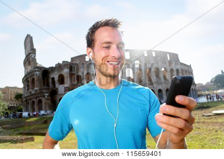 Happy male jogger listening music on smartphone against Colosseum. Smiling man is in sportswear. Handsome fit runner is enjoying music before workout on sunny day.