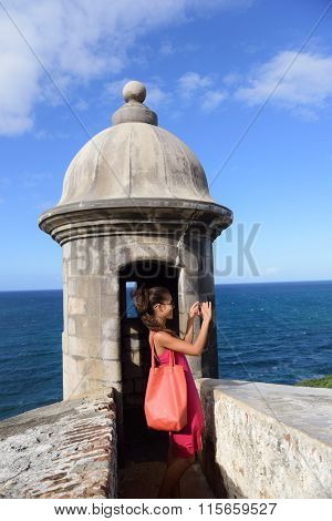 Puerto Rico woman taking pictures with smartphone at Old San Juan Fort Castillo San Felipe Del Morro. Asian tourist on her american travel visiting a famous landmark during summer vacations.