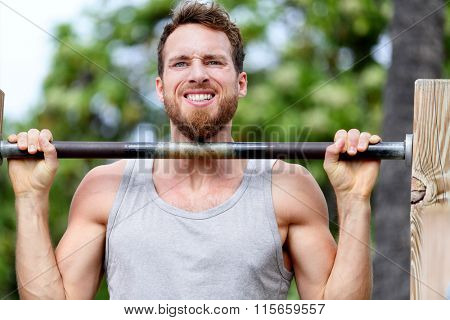 Crossfit fitness man exercising chin-ups workout. Young male adult trainer athlete portrait closeup with hands holding on monkey bars at outdoor gym doing a chin-up strength training muscle exercise.