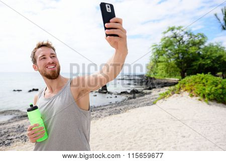 Fitness man taking selfie of himself after workout. Good looking young adult taking a self-portrait picture with his smartphone camera after exercising on a beach during summer vacation travel.