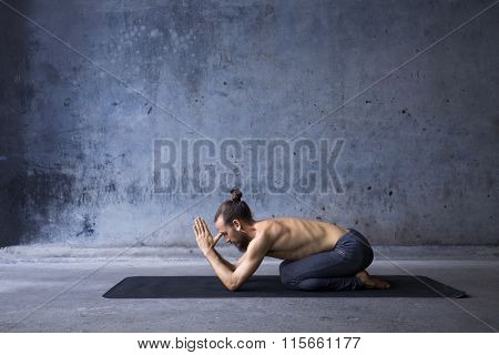Young man practicing meditation in a urban background