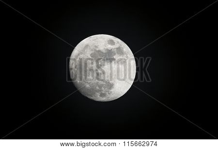 Image of a full moon shot during the evening shows the moonlight highlighting features of the planet.