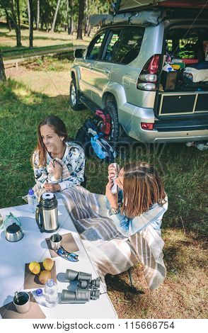 Woman playing harmonica with friend in campsite