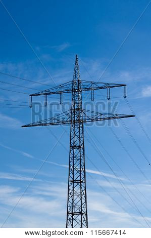 high-voltage electricity pylons against blue sky