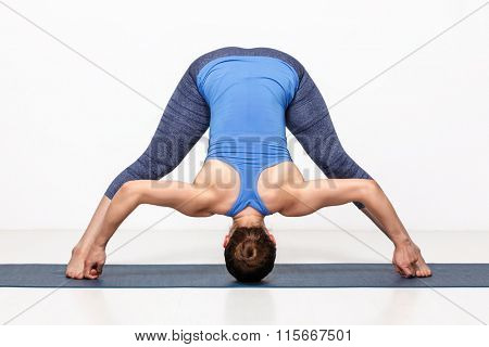 Beautiful sporty fit woman practices Ashtanga Vinyasa yoga asana Prasarita padottanasana D - wide legged forward bend D