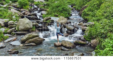 Woman practices balance yoga asana Vrikshasana tree pose at waterfall outdoors. Himachal Pradesh, India. Panorama