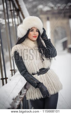 Woman with white fur cap and waistcoat enjoying the winter scenery near an iron fence