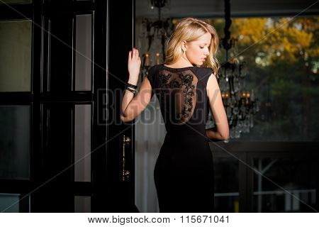 Woman in cocktail dress standing in a hallway