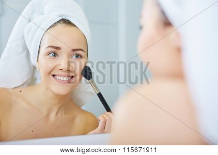 Beautiful young woman applying powder on her face