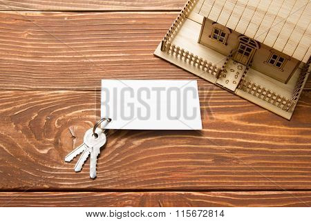 Real Estate Concept. Model house, keys, blank business card on wooden table. Top view.