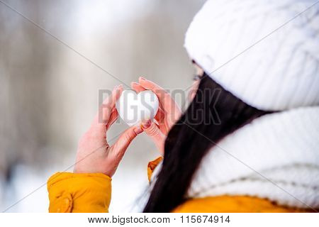 Heart of snow in the hands of a girl