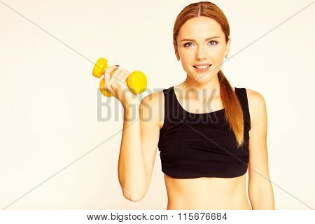 A Woman Holding A Yellow Dumbbell. Engaged In Fitness. Studio Photo