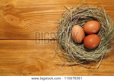The Composition Of Chicken Eggs Lying In A Nest Of Grass On A Panel Of Vintage Brown Boards With Fre